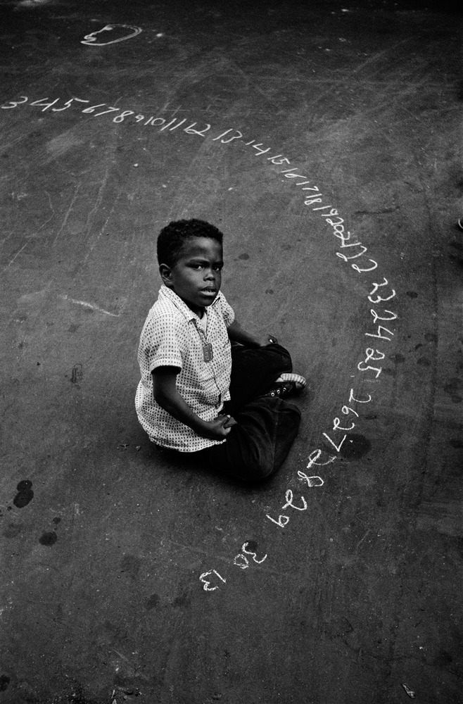 Boy writing chalk numbers - Coney island, Brooklyn, NYC, 1955.  By Harold Feinstein.