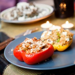 Moroccan spiced stuffed peppers Stuffed peppers are the bane of my life as a vegetarian. For some reason there appears to be an automatic mental connection between not eating meat and loving bland stuffed peppers that exists in omnivore's minds that overrides all rational thought. I'm here to tell you the same connection does not exist in our minds.  But if you do have a vegetarian friend and you insist on going down the stuffed pepper route, please, save their sanity and at least use this recipe..  Ingredients One pepper per person Two cups of cooked brown rice per pepper A lump of good quality goats cheese Half a cup of passata per pepper A generous handful of golden raisins A generous handful of sliced almonds A chunk of red onion per pepper A couple of garlic cloves A slug of olive oil A few stalks of flat parsley A dash of chilli powder A dash of cumin powder A dash of cinnamon powder or a cinnamon stick A small knob of grated ginger (jarred in fine too) A small knob of grated turmeric (or a dash of powdered) Salt Wash the rice and throw it in a pan of boiling water Halve and core the pepper and pop it in a medium-heat oven (with a little oil) to begin roasting. Leave for about 10 minutes or until you spot small dark spots developing.  Dice and sauté (I just learnt this means jumped, bounced) the onions with the olive oil in a large pan - it will later need to fit the cooked rice. When they begin to become transparent, throw in the minced garlic.  Turn the heat very low on the pan of onions, adding the ginger and turmeric with a slug of olive oil, and allow the flavours to fuse. I also add the raisins at this point to let them soak up some oil and become juicy. Once the rice has cooked, drain and rinse and add to the pan of onions. Add the passata and use a fork to mix the two without stirring (stirring will eventually turn the rice to mush) Chuck in your sliced almonds, spices, and salt to taste. When it is to your liking, stuff your peppers and crumble some goats cheese over the top. Whack your peppers into a hot oven until the cheese is golden on top.  Serve with a handful of roughly chopped parsley thrown over the top.