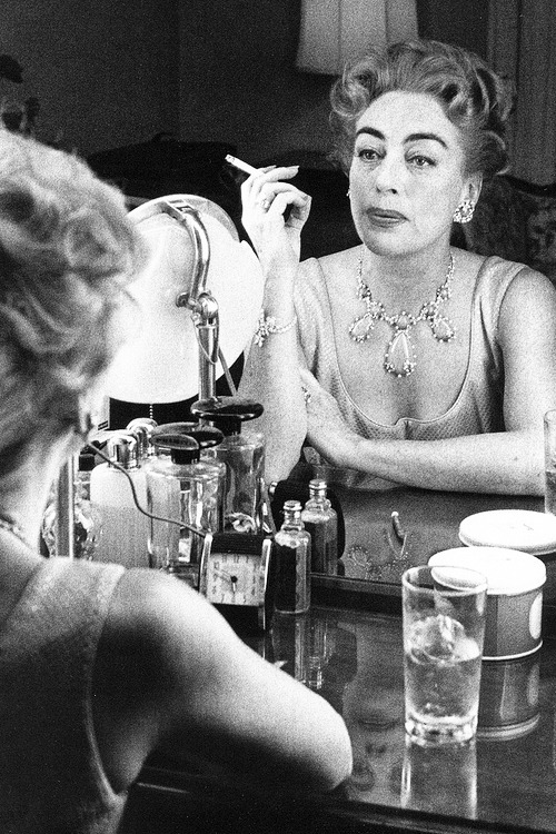 Joan Crawford gazing in the mirror, photographed by Willy Rizzo, 1959.