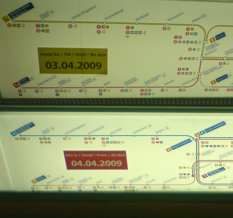 "Brussels Metro Map Changeover, April 2009 Here's an interesting pair of photos from 2009 that show two in-car strip maps that co-existed on Metro trains in Brussels. Together, they show the changes in the system that were occurring with the opening of track between the Delacroix and Gare de l'Ouest stations. Apart from a new look to the map, the system itself seems to have been overhauled completely, with the previous lines ""1A"" and ""1B"" becoming ""5"" and ""6"", amongst lots of other changes. Note also the four languages used on the informational stickers: French, Dutch, English and German! (Source: Daniel Sparing/Flickr)"