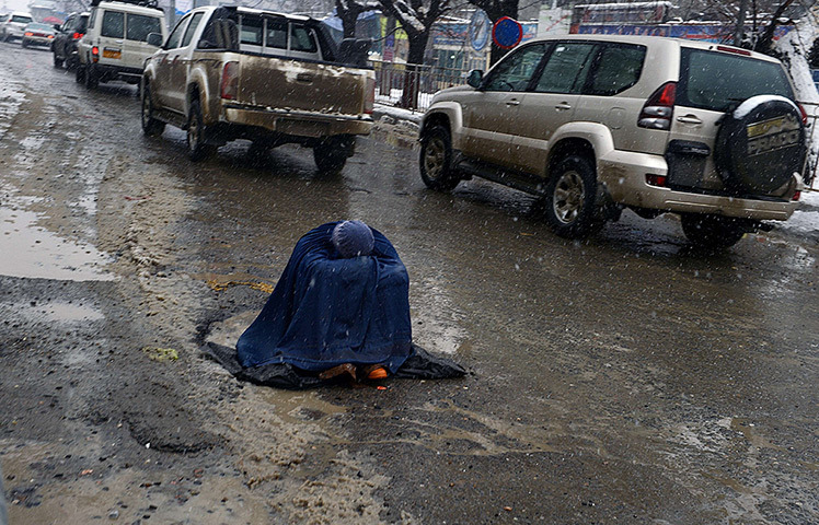 fotojournalismus:  An Afghan woman begs for alms as she sits on a slush-filled road as snow falls in Kabul on February 4, 2013. As winter sets in across Central Asia, many Afghans struggle to provide adequate food and shelter for their families. [Credit : Shah Marai/AFP/Getty Images]
