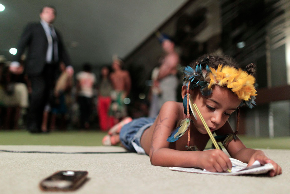 A Brazilian Indian boy draws on the ground during a protest where Indians from various parts of Brazil occupy the Chamber of Deputies in Brasilia April 16, 2013. They are protesting against a proposed constitutional amendment which gives power to Congress, rather than the Executive Branch, to decide on the demarcation of indigenous lands and reserves in Brazil. REUTERS/Ueslei Marcelino