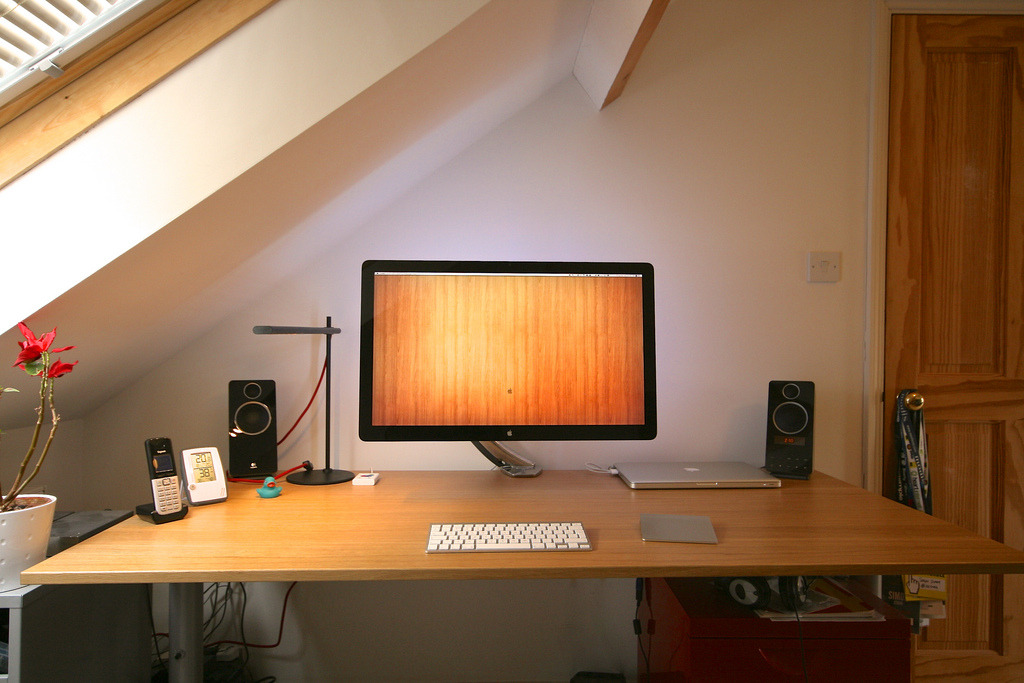 Simon Starr's neat setup and overhead sky-lighting.  The desk is an Ikea Galant with Signum cable trunking. The Cinema Display is mounted on an Ergotron MX LCD arm with a set of Dioder LED lights stuck to the back for some bias lighting.