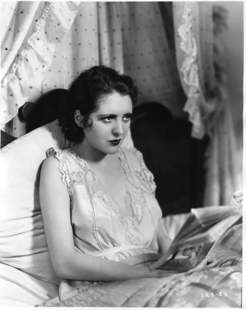 books0977:  Billie Dove (1903–1997) reading in bed, c.1930. In her heyday, this ravishing and highly photogenic star, known for her voluptuous femininity on the silent screen, rivaled that of Mary Pickford, Marion Davies and Clara Bow in popularity. She retired after only a few years into the talking picture era, however, and is not as well-remembered in today's film circles as the aforementioned.