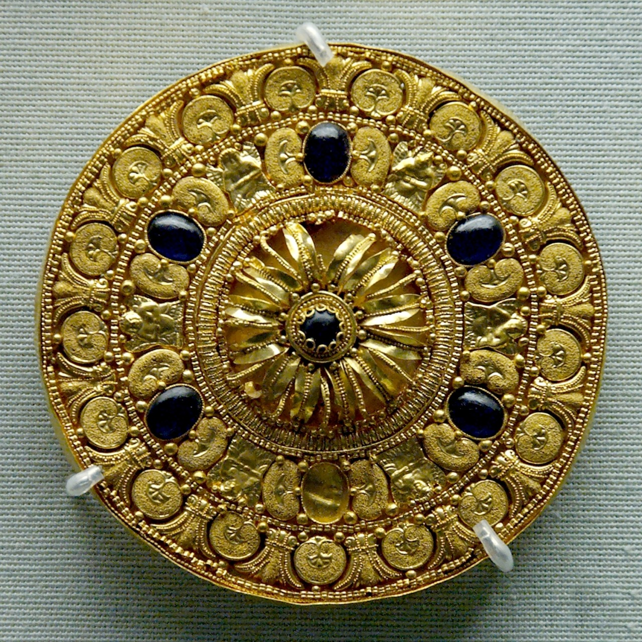 Ear-stud decorated with a rosette surrounded by concentric bands. Gold with vitreous glass paste insets, Etruscan artwork, 530–480 BC. Courtesy & currently located at the British Museum, London. Photo taken by Jastrow