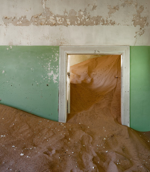 "Alvaro Sanchez-Montanes - Indoor Desert (2010) ""By the end of World War I, diamond mines in Kolmanskuppe, a site in the Namib Desert, ceased to be exploited. For over two decades it had been one of the wealthiest settlements in Southern Africa. During that time of splendour, German colonists who run the site had built their peculiar residences there evoking the architecture and décor of those in their homeland Bavaria. After it was closed down and its inhabitants left, Kolmanskuppe became a ghost town engulfed by desert sands. With his series Indoor Desert, Sanchez-Montanes enters these houses abandoned to the desert to unveil the serene enchantment that dwells in their chambers."""