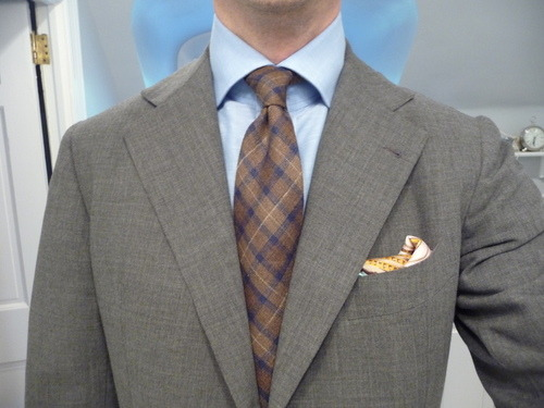 "Q and Answer: How to Wear A Pocket Square Aaron writes us to ask: I just started using pocket squares, and am not sure how to wear them best. Do you have any tips? Should they match my tie? How about my shirt? What's the best way to put them in the pocket? The guiding principle for pocket squares isn't too different from the guiding principle on how to dress well in general. You don't want to look like you didn't put in any effort (e.g. sweatpants, flip flops, and a dirty t-shirt), but you also don't want to look like you put in too much effort (e.g. looking like you stepped out of a fashion spread). Neither looks particularly natural or good. For pocket squares, that means not picking things at random, otherwise your square can become a distracting element, but also not matching things too closely, otherwise you'll look too studied. Instead, you want to your pocket square to be complementary to whatever else you're wearing. It should seem like you grabbed something at random (even though you didn't) and things just happened to work out well. Which means: Color (With Respect to Your Jacket): Make sure your pocket square is a somewhat distinctive piece. If you're wearing a navy sport coat, don't wear a navy pocket square. Instead, choose a color that stands out a bit more, such as burgundy, brown, or even white, but don't venture into something too loud. Again, you want this to look harmonious, not distracting. Color (With Respect to Your Tie): You never want your pocket square and tie to match. Tie + pocket square sets made from the same fabric should never be worn (let alone bought), but you should also not recreate this kind of look with whatever items you have on hand. Color wise, you want your pocket square to complement, but not directly mirror, your tie. There are two ways of thinking about this. The first is to choose something that subtly picks up a secondary color in your tie. So if you have a burgundy tie with navy and cream pencil stripes, you can choose a pocket square with a bit of cream to pick up the color in your tie. You would not want, however, to pick a pocket square in the exact same shade of burgundy, as this would look contrived. The other way of thinking about this is to pick a square in color that complements the main color of your tie. That can mean choosing things in a slightly different shade, or in a color that's either adjacent or directly across on the color wheel (navy put with a medium blue, or a dark green put with burgundy). This is somewhat trickier, however, because you run a greater risk of your pocket square either looking too thought out, or chosen at random. Best to judge on a case-to-case basis. Material: Silk or wool pocket squares can generally be worn with almost anything, although silk – especially cream or white silk – will look a bit dressier, especially if it has a ""wet,"" rather than a ""dry,"" finish. The shinier a square is, the more formal it can look. Linen is also very versatile, except maybe with tweeds and corduroy, where a silk or wool square might be better. The traditional white linen goes with pretty much anything, however. Cotton squares should be kept to summer suits, and wool has a cold-weather feel.  Personally, I like wearing a square in a different material than my tie. So wool squares with silk ties, silk squares with wool ties, etc. This is just a personal preference, however.  How to Fold: Gilt Manual covered the three main methods. I wear mine using a slightly different technique, which is shown here by Michael Alden. I find that produces a more appealing ""puff,"" but you can use whatever works best for you. Just don't use a needlessly fancy fold that makes your pocket square look like origami, and if you wear your pocket square with the points up, don't have them stick six inches into the air. Again, you want this element to be tasteful, harmonious, and charming, but not distracting. The Reliable White Linen: When in doubt, wear a white linen in the TV fold (or what Gilt Manual called the ""traditional fold""). You're almost always safe with that. (Pictured above: StyleForum member Manton)"