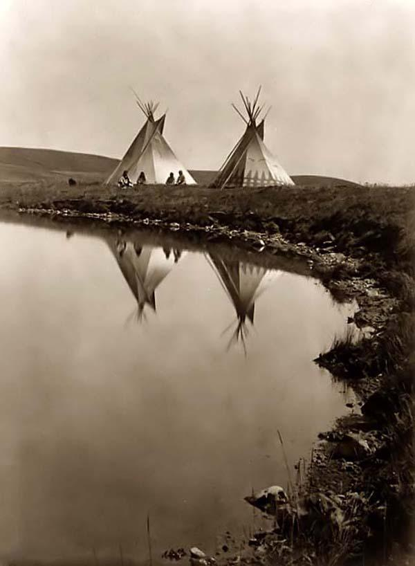 evocativesynthesis:  Tipis at the Waters Edge, Edward S. Curtis, 1910. Two tepees reflected in water of pond, with four Piegan Indians seated in front of one tepee. (via)