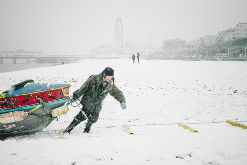 Hardy fisherman in the snow by lomokev Hardy Brighton fisherman dragging his boat up the beach in the snow. After I took this photo me and rockcakes did help him and gave it a push.