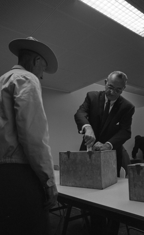 "November 8, 1966. Election Day. LBJ casts his vote at the Pedernales Electric Coop, Johnson City, Texas. The campaigning in these midterm elections has been fierce: after the 1964 Demoratic sweep, the Republicans have rebounded and are focused on issues of inflation;  the costs of the Great Society programs, and those programs' failures and disappointments; crime; racial strife and riots; a stalled Vietnam War effort, as well as its rising toll in money and lives; and the perceived ""credibility gap"" of the Johnson administration on many of these issues.   Democrats had enjoyed two years of a 295/140 majority in the House, and 67/33 majority in the Senate, and have controlled the majority of state governors and legislatures. Few Democrats expect to keep all of their contested seats: the question is how many they will lose. LBJ, for his part, was too good a student of politics to not expect a backlash against his policies—as early as February 1965 he warned his staff that their days of effective leadership were numbered.  LBJ Presidential Library photo #3849-30a. Public domain."