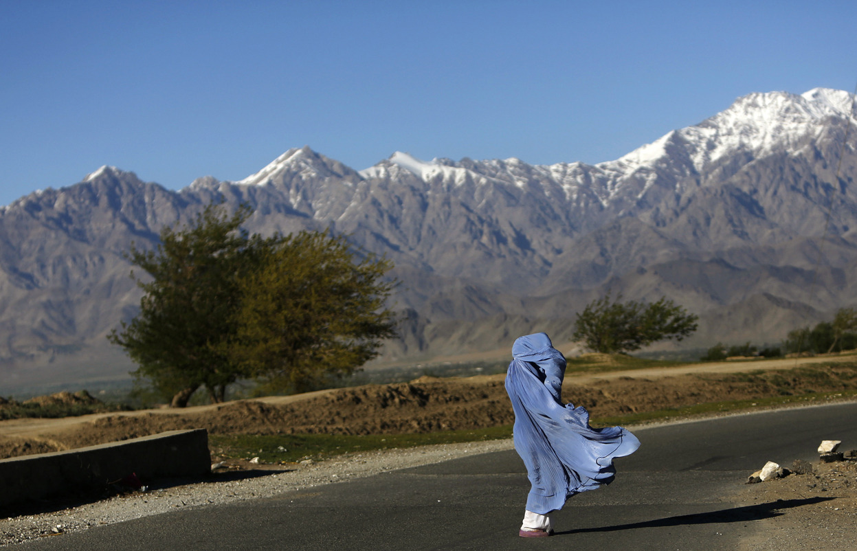 From Afghanistan: April 2013, one of 39 photos. An Afghan woman in a burqa walks along a road on a windy day on the outskirts of Kabul, Afghanistan, on April 16, 2013. (Reuters/Mohammad Ismail)