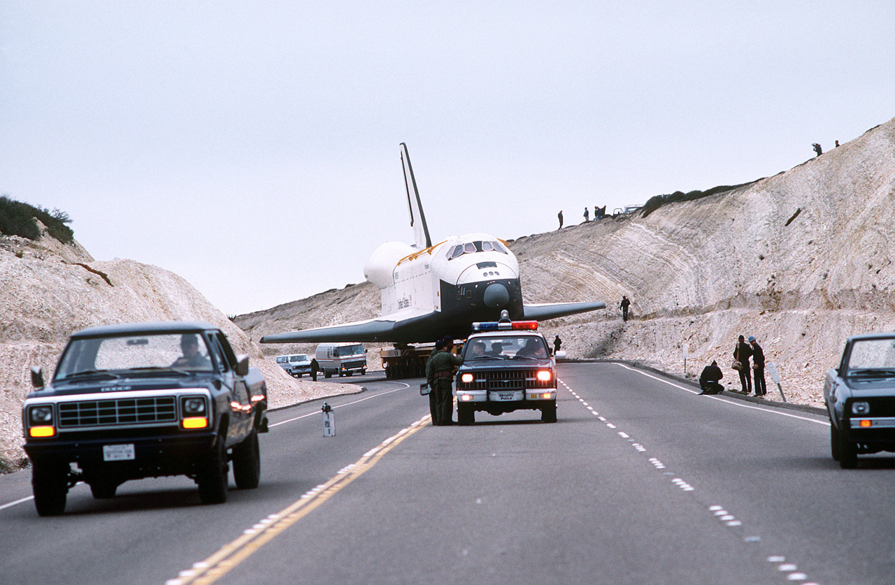 Make Way for Enterprise!  The Space Shuttle Enterprise passes through a hillside that has been cut to clear its wingspan. The orbiter is en route to Space Launch Complex Six aboard its specially-designed 76-wheel transporter, 02/01/1985  The Space Shuttle Enterprise was the first first full scale prototype.  It was built without a functional heatshield or engines and therefore could not achieve spaceflight.  A few weeks later the Enterprise was retired and sent to the Smithsonian Institution in Washington, DC.  The Enterprise was on display at the Steven F. Edvar-Hazy Center at Dulles International Airport until April 27, 2012 when it was ferried to New York City to become part of the exhibit at the Intrepid Sea, Air & Space Museum. (Coming off the anniversary of the most tragic week in Space Shuttle history, it seemed something lighter was called for.)