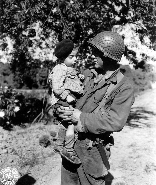 demons:  A US soldier carrying a French child in Trévières