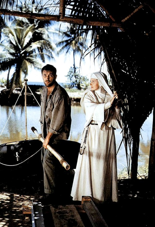 "Deborah Kerr and Robert Mitchum were a magical team.  The actress likened their work together to a perfect doubles pair at tennis.  Getting to know him in those first days on Tobago while filming Heaven Knows, Mr. Allison, as they sat on the ""soft pink sand."" Kerr recalled finding herself ""listening to an extremely sensitive, poetic, extraordinarily interesting man…a perceptive, amusing person with a great gift for telling a story, and possessed of a completely unexpected vast fund of knowledge…Bob was at all times patient, concerned, and completely professional, always in good humor, and always ready to make a joke when things became trying.""  Laura Nightingale, a wardrobe girl on the film, described Mitchum's great sensitivity toward his costar to journalist Lloyd Shearer: Sensing that her feet were hurting from the sharp rocks she'd been standing on, ""He just kneeled down, unlaced her white sneakers, removed them and massaged her feet.  It was lovely and compassionate the way he did it….Then he put her sneakers back on and said kind of brusquely to hide his tenderness, 'Gotta keep you alive for the next scene.'  Then he walked away.  Deborah was so touched she cried.""  Deborah became Bob's great platonic love. He would speak of her ever after as his all-time favorite actress and the ""only leading lady I didn't go to bed with"" — an exaggeration in any case, but meant somehow as a compliment.  When they met he had been expecting a prim Englishwoman like the rather frosty ladies she often played on screen, but Kerr turned out to be one of the boys.  She was a rare delight, warm, wise, earthy.  One time she was rowing a raft in open water during the tortoise-chasing scene, John Huston constantly shouting, ""Faster! Row faster!""  The wooden oars split in half in her hands, and Kerr, in her damp nun's habit, screamed in fury, ""Is that fucking fast enough?  Mitchum, floating nearby, swallowed a gallon of saltwater laughing.   One day, an inspector from the Catholic Legion of Decency arrived on set as Huston was preparing a scene between Mitchum and Kerr. Huston greeted the priest and then called for ""Action.""  Director and crew were deadpan as Bob and Deborah spoke their lines, then moved closer together, Mitchum sliding his hand under nun Kerr's breasts while she cupped his buttocks and they began to kiss with open-mouthed abandon.  The Legion of Decency man's eyes widened, he grasped at his heart and screamed, ""What is going on there?!""  ""No talking, Father,"" said Huston. ""Dammit, now you've gone and ruined a perfectly good take.""   —Excerpt from Robert Mitchum: Baby I Don't Care"