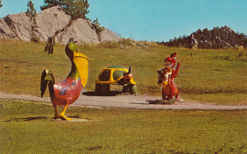 Flintstones Bedrock City - Custer, South Dakota Bedrock City, located on 30 acres, just outside of Custer, South Dakota, opened in 1966 by two local cement plant owners with an idea to build a replica of the popular Flintstones town of Bedrock. The town features all the popular characters, their houses, Main Street, a City Hall, a Fire House, a working Cimena, a radio station, grocery store, police department and a Flintstones version of Mt. Rushmore (located nearby) called Mt. Rockmore. Originally, the town and characters were made of cement but the majority of them have been replaced by fiberglass replicas of the original. There is also a campground located behind the park that features an arcade, laundry, swimming pool, playground and putt-putt golf course. Guide Note: Check out Roadside America and the Bedrock City website for more information. * * *  Jordan Smith is the guide to ephemeral America for The American Guide. He currently works for the University of Notre Dame during the day and scans at night. He lives in South Bend, Indiana and you can find him on Flickr, his blog, or one of several Tumblr sites.