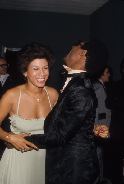 vintageblackglamour:  Stevie Wonder (who turns 63 today!) shares a laugh with his friend, Minnie Riperton, at a party in 1975. Photo: Michael Ochs Archives/Getty.