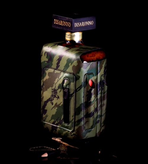 "Maharishi x Disaronno x Bagjack - Camo Bottle Sleeve You wanna make a girl's drink a little bit more manly than adding coke or cranberry juice? Well this bottle sleeve may just do the job. In collaboration with Maharishi, Italian liqueur Disaronno and German messenger bag designers Bagjack, what you have is a ""conceptual multi functional bottle sleeve"" which contains little quirks such as 24 karat gold plated and waterproof USB stick and a few fancy pens. The sleeve is designed in a high quality leather printed in the Maharishi ""Bonsai Forest"" camo. A limited piece with only 50 available globally, your manly drink is waiting for you…  image courtesy of Maharishi"