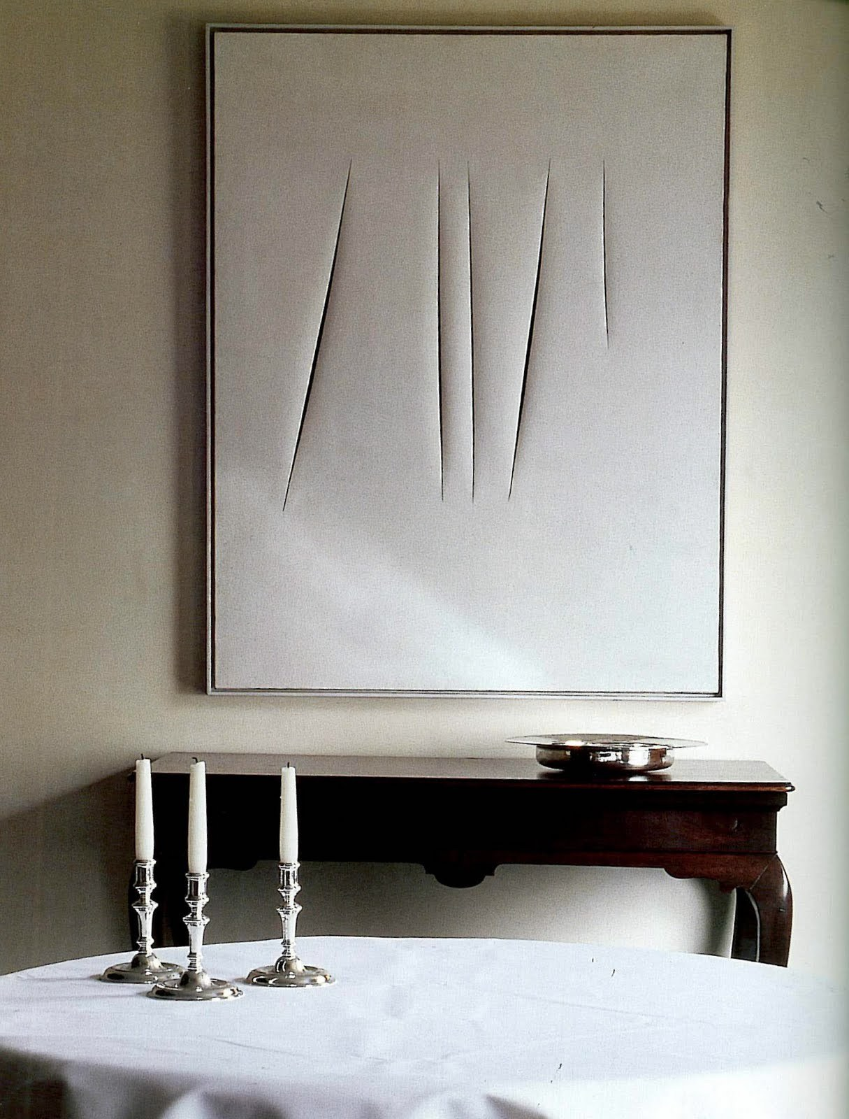 Interior design by Axel Vervoordt, with work of Lucio Fontana on display.