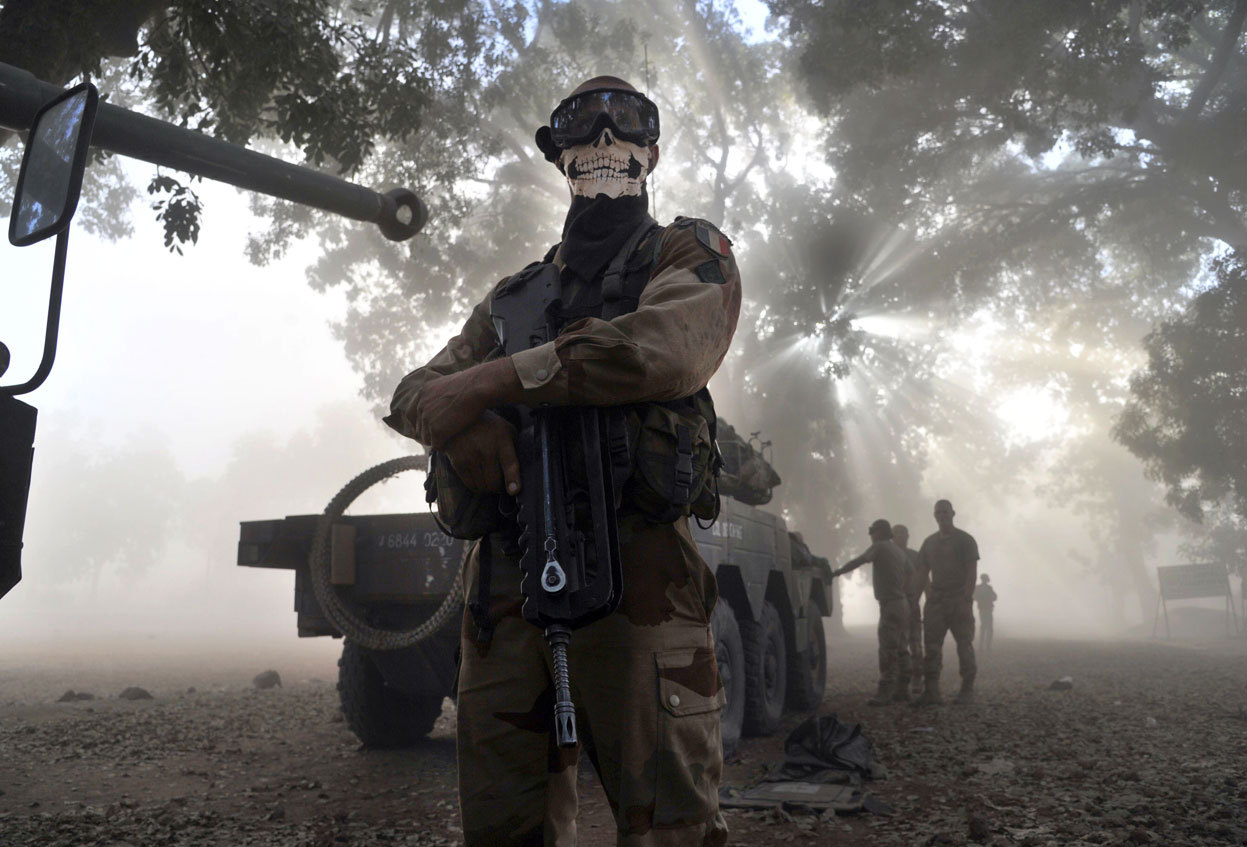 "From The Conflict in Mali, one of 36 photos. A soldier of the French foreign legion wearing a skeleton mask stands next to an armored vehicle in a street in Niono, Mali, on January 20, 2013. French Defence Minister Jean-Yves Le Drian said today that the goal of France's military action in Mali was to retake control of the entire country from Islamist militants who have seized the north. ""The goal is the total reconquest of Mali. We will not leave any pockets"" of resistance, Le Drian said on French television. (Issouf Sanogo/AFP/Getty Images)"