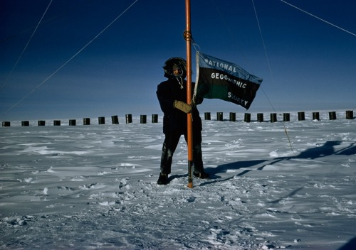 1957 | SOUTH POLE, ANTARCTICA - National Geographic magazine's Thomas Abercrombie, first correspondent to reach the South Pole, flies the Society's flag from the Pole while reporting on the International Geophysical Year of 1957-58. (Photo by Thomas J. Abercrombie)