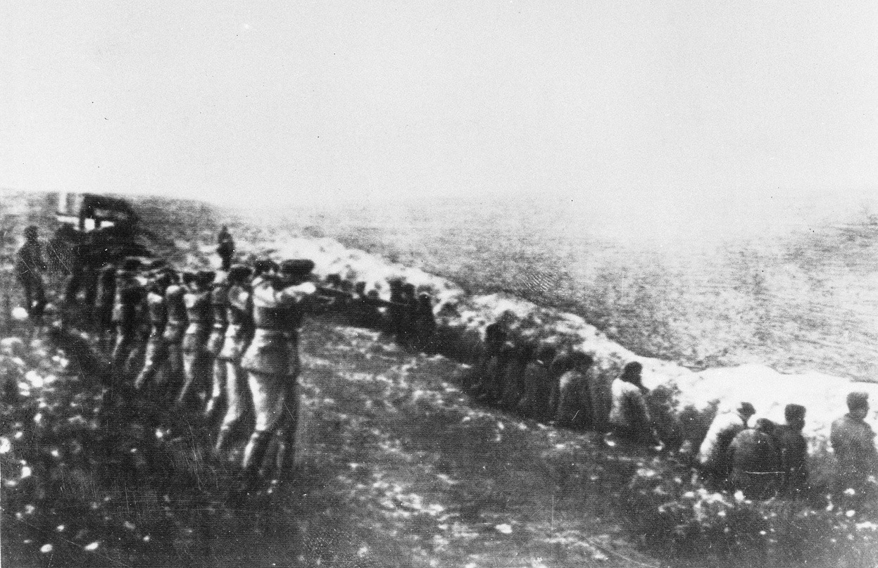 """""""This photo was taken from the body of a dead Germany officer killed in Russia, showing a German firing squad shooting Soviet civilians in the back as they sit beside their own mass grave in Babi Yar, an infamous ravine in the Ukrainian capital of Kiev, in 1942. Between 1941 and 1942, an estimated 100,000 to 150,000 Jews, Soviet prisoners, communists, gypsies, Ukrainian nationalists and civilians were executed by the Germans in Babi Yar."""" (AP)"""