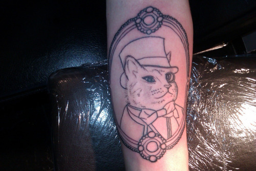 started this cat in a hat wearing a monocle and bowtie…. tattooed by vikki at eerie ink in walsall, uk
