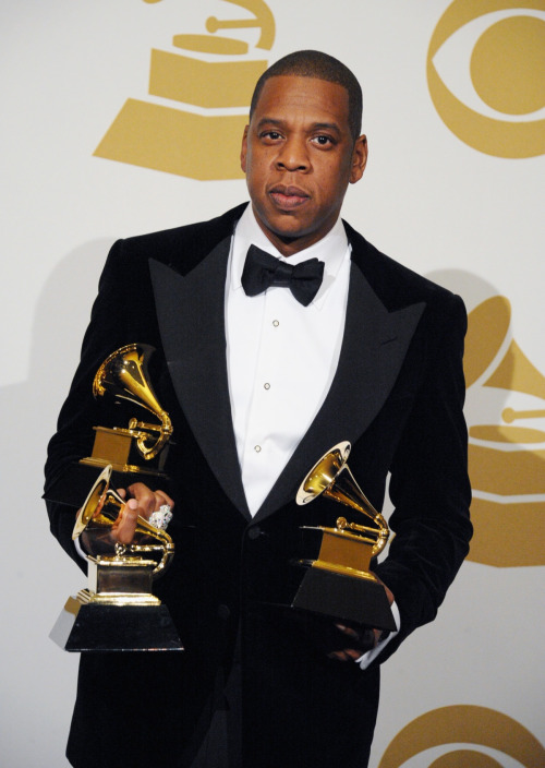 Jay-Z, looking dapper in a Tom Ford velvet blazer and tuxedo, shows off his three Grammy Awards backstage. Hov now has 17 Grammy Awards in the trophy case at home.