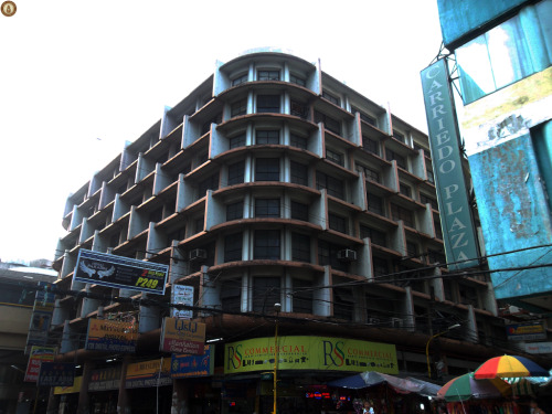 The Last Antonio Building at Avenida Located at the corner of Avenida Rizal and Carriedo Street in the old Downtown Manila, this is the last standing building in the Avenida Area designed by National Artist Pablo Antonio after the Ideal Theater was demolished in the late 70s and the Galaxy Theater was demolished in 2008. Built in the early 1950s, modernist architecture (International Style) is starting to seep into the Philippine Landscape, the building employed curved bands (horizontal and vertical) to serve as sunshades. The building is also curved in a streamline in the corners, a style derived from the streamlined Art Deco that was prevalent during the late 1930s. The building is mainly used for commercial use, and it was one of the first buildings that enabled the old Downtown Area to revive economic activity in the area after the destruction of the war. It is still used as a commercial building though its facade facing the Avenida is already blocked by the elevated tracks of the LRT 1. PS: The original design of the LRT 1 was at street level rail tracks like the old PNR lines. But one Marcos swerve and it became elevated. Elevated tracks eliminated the conflict from other modes, enabling the trains travel much faster than if it is at street level. Enabling LRT to travel faster killed the Avenida and Escolta area.