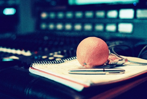 mrtoday:  photo six Just an orange on some recording notes. One of us decided to be healthy one day in the studio and eat an orange. My guess is it was Pat's… This was taken in the last week of recording the album. We had a few days of just listening back and writing down notes on all the songs to make sure we had everything we wanted on the songs. I bought a new lens for my camera in the studio and i was testing out the focus. You can see the recording console out of focus in the back and the orange and paper as in focus as i could get it…
