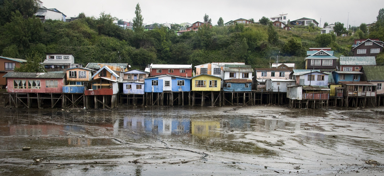 Palafitos Traditionally, fishermen on the island of Chiloé lived in houses built on stilts called 'Palafitos' to avoid changing tide currents along shorelines. Palafitos also gave residents the ability to move when they felt like relocating. These events were called 'Mingas de Tiradura' and were usually a community effort where neighbors joined their oxes to pull a house to its new plot of land, sometimes floating the entire structure over water to do so. Tiraduras still exist, but occur less often as the number of palafitos have declined over the years and island communities have become modernized. Regardless, the structures remain as one of Chiloé's defining characteristics and are preserved as some of the last examples of the region's independent fishing roots. Castro, Isla Grande de Chiloé, Chile - © Diego Cupolo 2012