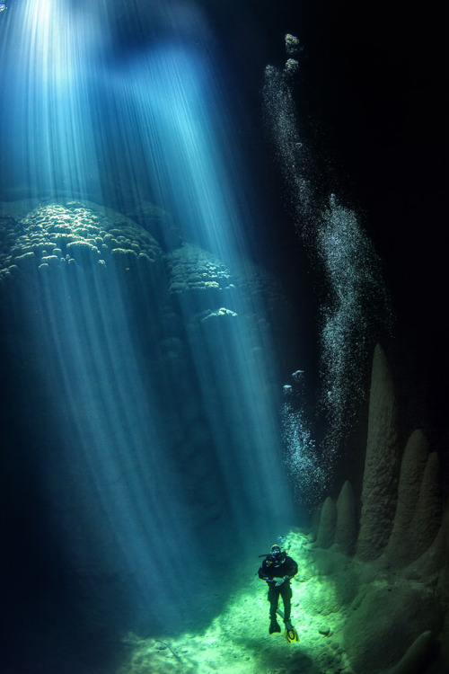 geniusofthehole:  Anhumas Abyss by Marcio Cabral  Anhumas Abyss is a cave 23km from the city of Bonito Mato Grosso do Sul, Brazil. Access is by a gap that exists in the Rock through vertical Rappelling techniques. To the base of the cave is 72 meters of vertical drop, until the deck on the lake of clear water. That can reach 80m. depth. During some days of the year the sun passes through the small opening of the cave, producing a beam of light that illuminates the cave for a few hours.
