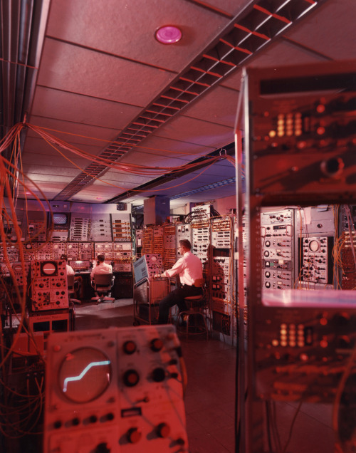 brookhavenlab:  It's hard not to marvel at the crimson glow of 1966 science.  Before the digital revolution converted complex workspaces into flat-screen monitors and unobtrusive computers, the control rooms of big experiments were the ultimate in analog awesome. Our Alternating Gradient Synchrotron—still accelerating particles here at Brookhaven after 53 years—featured just such an array of custom-built electronics. Just look at all those knobs, dials, and oscilloscopes.
