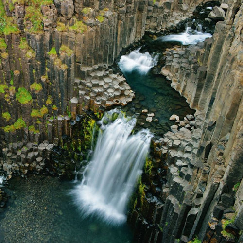 hanjeanwat:  Hexagonal rocks-WUT: The columns form due to stress as the lava cools. The lava contracts as it cools, forming cracks. Once the crack develops it continues to grow. The growth is perpendicular to the surface of the flow. Entablature is probably the result of cooling caused by fresh lava being covered by water. The flood basalts probably damned rivers. When the rivers returned the water seeped down the cracks in the cooling lava and caused rapid cooling from the surface downward. The division of colonnade and entablature is the result of slow cooling from the base upward and rapid cooling from the top downward. (via Hexagonal rocks)  Columnar basalt is just too awesome.