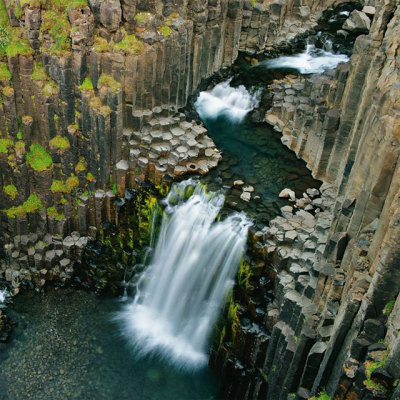 This is an Icelandic waterfall called Litlanesfoss and the naturally occurring rock formation is columnar jointed basalt. (via Kotkke: Hexagonal rocks)