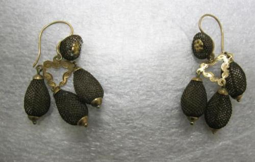 Mourning earrings, 1899-1902 US (Old Salem, NC), the North Carolina Museum of History  EARRINGS, TEARDROPS OF WOVEN BROWN HAIR ATTACHED TO DECORATIVE VERMEIL TRIANGLE, ATTACHED IN TURN TO VERMEIL MEDALLION MOUNTED ON CIRCLE OF WOVEN HAIR; FRENCH HOOKS FOR PIERCED EARS. HAIR JEWELRY AND ART WERE POPULAR FROM THE LATE 18TH UNTIL THE EARLY 20TH CENTURIES FOR COMMEMORATIVE, MEMORIAL (MOURNING), SENTIMENTAL, AND DECORATIVE PURPOSES. DURING THE MID-19TH CENTURY MANY WOMEN TOOK UP THE HOBBY OF MAKING HAIR JEWELRY AT HOME. EARRINGS OF THIS STYLE (TABLE-WORKED DANGLES) WERE PARTICULARLY POPULAR 1850-1870. THIS PIECE WAS MADE A LITTLE LATER THAN TYPICAL FOR THIS FORM.