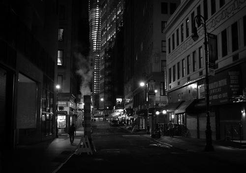 "New York City at night - Financial District street with a smoke stack.  At night after the multitudes have retreated to their homes away from the buildings and streets that hold them close during the day the city relaxes shaking the dust of the long day from its concrete limbs.  The street lights flicker like dream-heavy blinks of an eye while smokestacks exhale world-weary breaths of smoke into the yawning night air.   —-  View this photo larger and on black on my Google Plus page  —-  Buy ""Smoke - Night - New York City"" Posters and Prints here, email me, or ask for help."