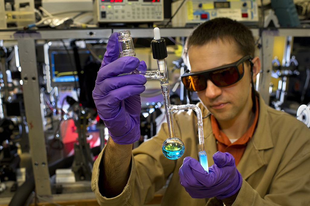 Image description: Scientist Dmitry Polyansky examines a vial containing a specialized catalyst designed to help convert solar energy into fuel. Producing clean-burning hydrogen fuel from just sunlight and water requires custom-built catalysts for water oxidation — the part of the water-splitting process that generates oxygen atoms. A tiny amount of the solid catalyst, developed in collaboration with the University of Houston, dissolves and turns the water that lovely shade of blue. Photo from Brookhaven National Laboratory.