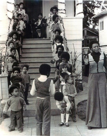 Huey P. Newton (seated on porch) watches Donna Howell and the children of the Intercomunal Youth Institute. Photo: Lauryn Williams, 1972   The Oakland Community School (OCS) was one of the most well-known and well-loved programs of the Black Panther Party. Point Five of the Black Panther Party's original 1966 Ten Point Platform and Program, emphasized the need to provide an education that, among other things, taught African American and poor people about their history in the United States. To this end, the Oakland Community School became a locale for a small, but powerful group of administrators, educators, and elementary school students whose actions to empower youth and their families challenged existing public education concepts for black and other poor and racially marginalized communities during the 1970s and 1980s. Historically, however, the educational programs of the BPP started long before the OCS with the vision of the party's leaders. As early as 1967 Huey Newton and Bobby Seale began speaking to high school youth at San Francisco/Bay Area public schools. In 1969, in U.S. cities where there were strong BPP chapters, liberation schools staffed by volunteer party members opened in storefronts, churches and homes. These after-school programs were created to give academic support to black and other poor youth. These community school programs created a forum for young people to explore a factual history of America and a sense of connection and community. (via Erika Huggins)