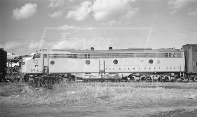 CMStP&P EMD diesel locomotive 37-A and coach 385 on Sunday-only passenger train 113 arrived at 1:55pm.  Walworth, WI  March 15, 1964 #commuter train#milw#milwaukee road#1964#chicago#trains#passenger train#history#walworth#wisconsin
