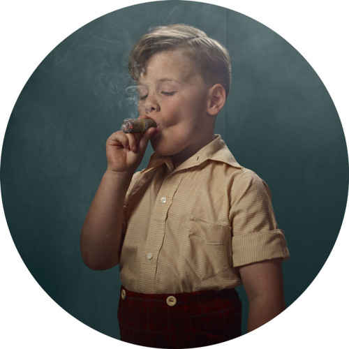 "bombing:  Smoking Kids by Frieke Janssens    ""A YouTube video of a chainsmoking Indonesian toddler inspired me to create this series, ""Smoking Kids"". The video highlighted the cultural differences between the east and west, and questioned notions of smoking being a mainly adult activity. Adult smokers are the societal norm, so I wanted to isolate the viewer's focus upon the issue of smoking itself. I felt that children smoking would have a surreal impact upon the viewer and compel them to truly see the acts of smoking rather than making assumptions about the person doing the act."