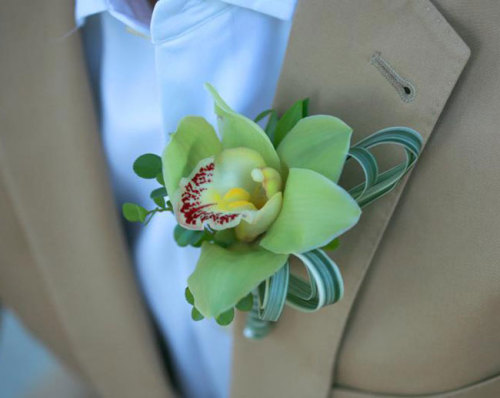 For the groom - a green cymbidium blossom accented with varigated grasses and button shaped leaves. Image by Castaldo Studio