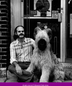 Man and dog sitting in front entrance to Peter's Pharmacy, Milwaukee. via: Historic Photo Collection, Milwaukee Public Library