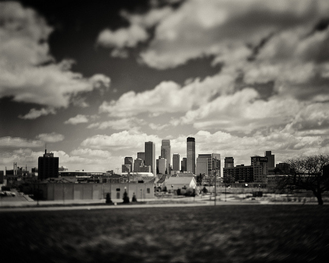 "This is a photograph of a city, Minneapolis, in the daytime. on Flickr.Crown Graphic | 135mm f/4.7 Optar (wide open/titled) | Arista/Foma 100 (@80) | R60 filter | Grad ND filter | Rodinal (1:50) Recently, I've been taking Highway 55 to downtown which takes you through a not-so-nice part of town that has some great vantage points of the skyline. I think it's interesting to see the city with the industrial part of town in the foreground. Don't get me wrong, the Stone Arch Bridge and all is a nice area, but you'll run into about 500 other photographers there, aiming their cameras at the same place you are. This view (above) had always intrigued me as I drove by, so last weekend I decided to venture through the maze of road construction from my apartment in Longfellow to this spot, on a dead end of a road that runs parallel to Olson Memorial Highway (the other name for 55). I was standing in a field of spring-long grass and it was windy as hell. My camera tipped over once with the lens extended and everything, but thank goodness for cameras built like tanks. All I had to do was pick it up and re-level it and it was good to go. I suppose I'll tire of this ""tilting"" business sooner or later; I mean, I can do it whenever I want on Instagram. But there's something like the real thing (notice the swirl of the old, wide open, tilted lens in the bottom corners) that makes it special. The ability to isolate an important element (the skyline) in a scene while also noting its context (Industrial North Minneapolis) is the key to this technique. The 135mm lens is the equivalent of about a 40mm lens on a 35mm camera. It's a pretty wide normal lens, so taking landscape shots like this can be difficult if you don't have a way of isolating your subject, be it through a vignette, good light, or tilt (or all of the above). All analog all day."