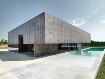 House in Urgnano by Matteo Casari Architetti Concrete box rises off the ground, offering a striking contrast with glass and azure water of the swimming pool.