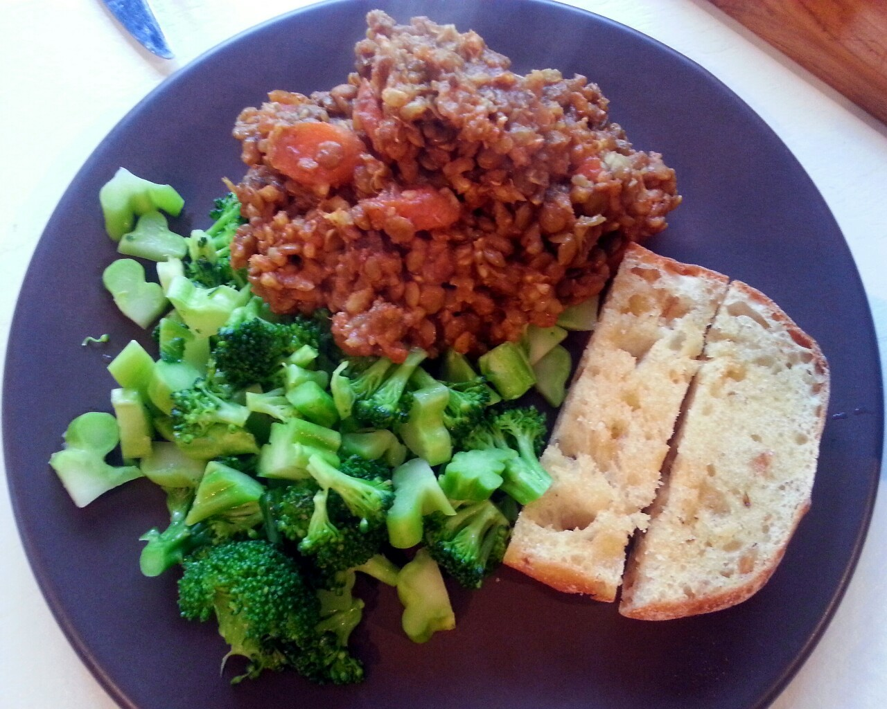 Slow Cooker Curried Lentils with Broccoli and Garlic Bread   I used my slow cooker, which I'm not really good at using as it turns out. Anyway, throw 2 cups lentils, 1 cup brown rice, about two or three carrots, and a chopped onion in the slow cooker with at least 4 cups water, maybe even 5 cause mine could have used more water to soak up. Veggie broth would be even better if you have it. Add 2 tbs curry powder, 1 tbs cumin, 1 tbs garlic, and cayenne, salt, and pepper to taste. Turn the cooker on low for 6 hours.   Slice a baguette down through the middle lengthwise and spread more Earth Balance and Garlic powder on it - or minced fresh garlic would be preferred. Pop that baby in the oven at 350 until it's warm and toasty.  When it's time to eat, chop up a head of broccoli and steam on medium heat with about 1 tbs Earth Balance for only a few minutes, until vivid green and just barely tender.   Have a delicious night!   Ps: if you don't have a slow cooker, or if you think they're stupid, just cook the lentils and rice at a simmer for about 45 minutes or until water is soaked up.