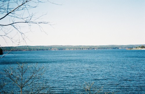 "JORDAN LAKE, NORTH CAROLINA Spanning 21 square miles and nearly three counties, and smack-dab in the middle of North Carolina is the beautiful Jordan Lake. The reservoir and dam are two of the state's most treasured and important resources; not only is the area a protected state park and popular recreation site, but it's also tasked with flood and water quality control, and is responsible for supplying water to the capital metro area. Jordan Lake's history is an interesting one. Various cultures have called the area home for over ten centuries; both Revolutionary and Civil War troops marched through. But in the second half of the 20th century, big changes came. Twenty years after a particularly damaging tropical storm in 1945, the Army Corps of Engineers was handed the ""New Hope Lake Project"" (eventually renamed B. Everett Jordan Lake after the former Senator, who—little known fact—was eventually unseated by comedian Zack Galifianakis's uncle). The Engineers were tasked with studying flood control and water resource needs in the area and as a result in the decade between 1973 and '83, the New Hope and Haw Rivers were dammed and flooded. Farming families were relocated; roads were rerouted or wholly covered by water. To this day, when the water is low enough, old roads and forgotten bridge parts create pseudo-sandbars for birds to sun themselves on. Now a State Recreation Area, Jordan Lake's shores are protected from development. At the south end is the impressive dam, where the surface can be calm or full of churning white caps, depending on the day. The past several years have seen a grassroots movement to clean up the scourge of litter plaguing Jordan Lake's shores—a prime example of the place the area holds in the hearts of its residents. The bald eagle is the lake's official animal, and the area is home to many other recognizable North American woodland animals. Visitors can fish, swim, sail, hike, hunt or camp. Boasting multiple boat ramps, canoe launches, two beaches, piers (including one that's wheelchair-accessible), playgrounds, campgrounds, and a privately-owned marina, it's one of the best places in the state to spend a day. This author, for one, is happy to call Jordan Lake home. * * *  Brittany Kearns is a Guide to North Carolina. An honorary Southerner, she was born in New Jersey, but now calls rural Chatham County home. She's got a degree in anthropology, a love for documentary photography and takes film over digital any day. Follow her on Tumblr at thebeekearns.tumblr.com and check out her portfolio at BrittanyKearns.com."