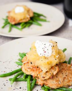 Potato pancakes topped with apple sauce over buttered green beans On an unrelated note, I don't understand people who don't enjoy being in the kitchen. If you're one of those people, open the window if it's a warm evening. Pour a large glass of red wine. Dim the lights. Play Louis Prima's Just a Gigolo. Louder. This is 'cooking'. Isn't it wonderful? This recipe is a classic, a budget-friendly staple in various cuisines. I didn't plan to make it: I just rummaged around the fridge and happened upon a couple of potatoes, an egg, half a bag of apples and some frozen green beans. Food-fate, some might say.  The cheese, optional if you prefer to be healthy, can almost any hard cheese - chedder goes particularly well with apple, gruyère is nutty and heavenly (my personal favourite for this), even halloumi or mozzarella would work well.  Ingredients  A couple of large of potatoes (one per serving)  One small to medium white onion (size dependent on how many servings you are making) One egg A cup of flour 20 grams of cheese per serving Paprika  Salt and pepper Olive oil  For the apple sauce One apple per serving Water  Ground nutmeg  A dash of sugar or sugar alternative  To serve Green beans, frozen or fresh  Butter Salt  Sour cream    Peel, core and chop the apple a heavy saucepan with a centimetre of water and place on a medium to high heat, adding water if needed. The apples should cook and disintegrate rapidly without browning or burning. I keep my sauce quite chunky, you may prefer to have a smooth consistency. Once the sauce is ready, add a dash of sugar (or honey / agave syrup) to taste and a pinch of nutmeg. Skin and grate the potatoes and mix in a large bowl with finely chopped white onion and the grated cheese. Break the egg into the bowl and stir thoroughly. Slowly sift in the flour, tablespoon by tablespoon, until the flour/egg mixture is the consistency of a condiment (is that vague enough?) Chuck in a little paprika. Heat the oil in a large frying pan (throw a little of the mixture in to test the heat - it should sizzle and turn golden and cripsy without burning) Using a spoon or ladle place dollops of the mixture in the pan and flatten.  Once both side have fried, I place the pancakes on kitchen towel to soak up the excess oil. Once they are all cooked, I pop them in an oven on a medium heat to ensure they cooked through and crisp them a little more. Depending on the size, this will usually take between 5 - 8 minutes.  As the pancakes bake, flash-boil the green beans to keep them crunch and fresh. Once drained, stir in a tablespoon of butter or oil and a dash of sea salt.  To serve, heap some green beans on a place and place a couple of pancakes on top. Smother with apple dauce and a touch of sour cream.