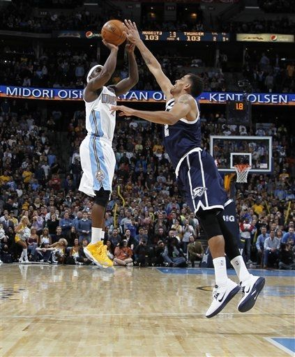 Denver Nuggets guard Ty Lawson, left, shoots the winning basket over Oklahoma City Thunder forward Thabo Sefolosha, of Switzerland, in the fourth quarter of the Nuggets' 105-103 victory in an NBA basketball game in Denver.