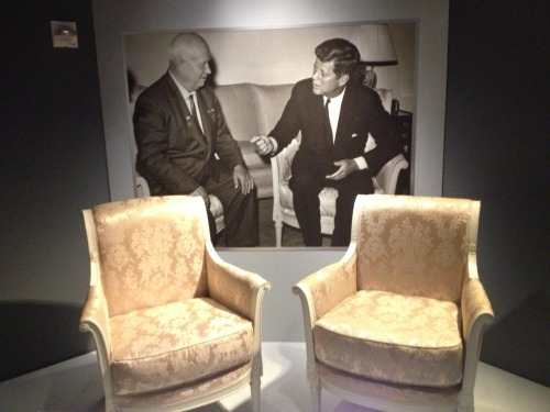 jfklibrary:   Two days and counting until we launch our latest exhibit – To The Brink: JFK and the Cuban Missile Crisis! We're adding a few finishing touches, but here's a sneak peek: the chairs used by President Kennedy and Soviet Premier Nikita Khrushchev in their 1961 Vienna meeting. The iconic photo of their meeting can be seen in the background.  To The Brink: JFK and the Cuban Missile Crisis opens April 12 at the JFK Library. Watch here to learn more about the exhibit: http://www.youtube.com/watch?v=KO9YrVKc7Tc&feature=youtu.be  Yes!