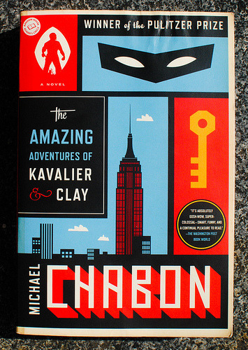 coverspy:  The Amazing Adventures of Kavalier Clay, Michael Chabon (F, 20s, using finger to follow text while reading, G train) http://bit.ly/16zyq1J  I like this so much better than the cover I own.  L'envy.